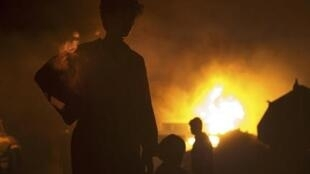 Truck drivers stand near their burning vehicles, which were carrying supplies to foreign forces in Afghanistan.