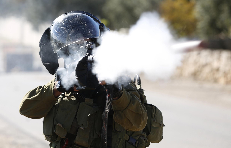 Un soldat israélien tire une cartouche à gaz, pendant des affrontements avec des militants palestiniens, le 28 mars près de Ramallah.