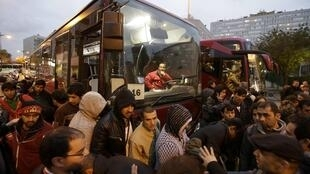 Migrants board buses after their evacuation from the Lycee Jean Quarré