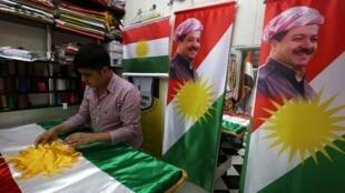 پرچم  اقلیم خودمختار کردستان عراق با عکس مسعود بارزانی رئیس دولت این اقلیم.