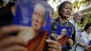 Des bouddhiste thaïlandais rendent hommage à leur patriarche dans les rues de Bangkok.