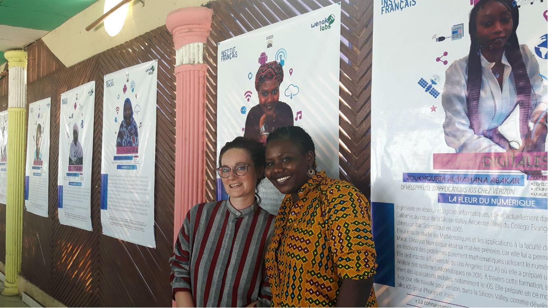 """Marie Perret (Institut français du Tchad) et Sandrine Naguertiga (WenakLabs) devant la galerie de photos de l'exposition """"Femmes digitales"""" sur la terrasse de WenakLabs, en plein cœur de N'Djaména."""