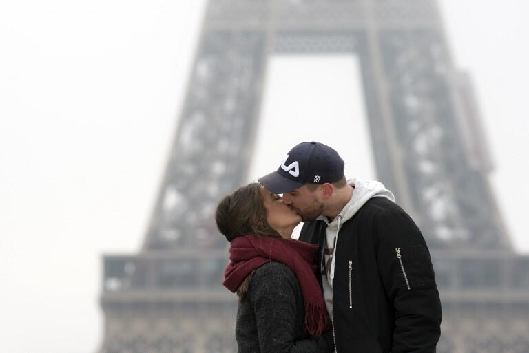A couple kisses at the Trocadero Esplanade, with the Eiffel Tower in the background, on Valentine's Day 2018