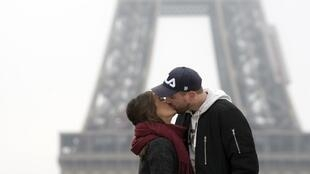 A couple kisses at the Trocadero Esplanade, with the Eiffel Tower in the background, on Valentine's Day, February 14, 2018, in Paris.