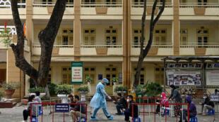 Vietnamitas esperan para someterse a un test de diagnóstico de coronavirus cerca del hospital Bach Mai, en Hanoi, el 30 de marzo de 2021