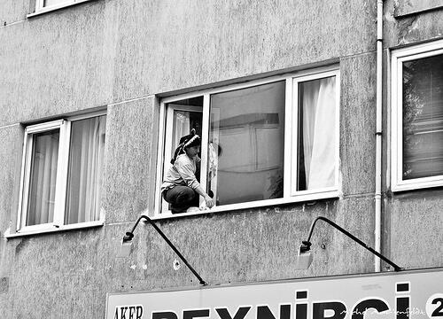 Una mujer limpiando vidrios en un edificio.