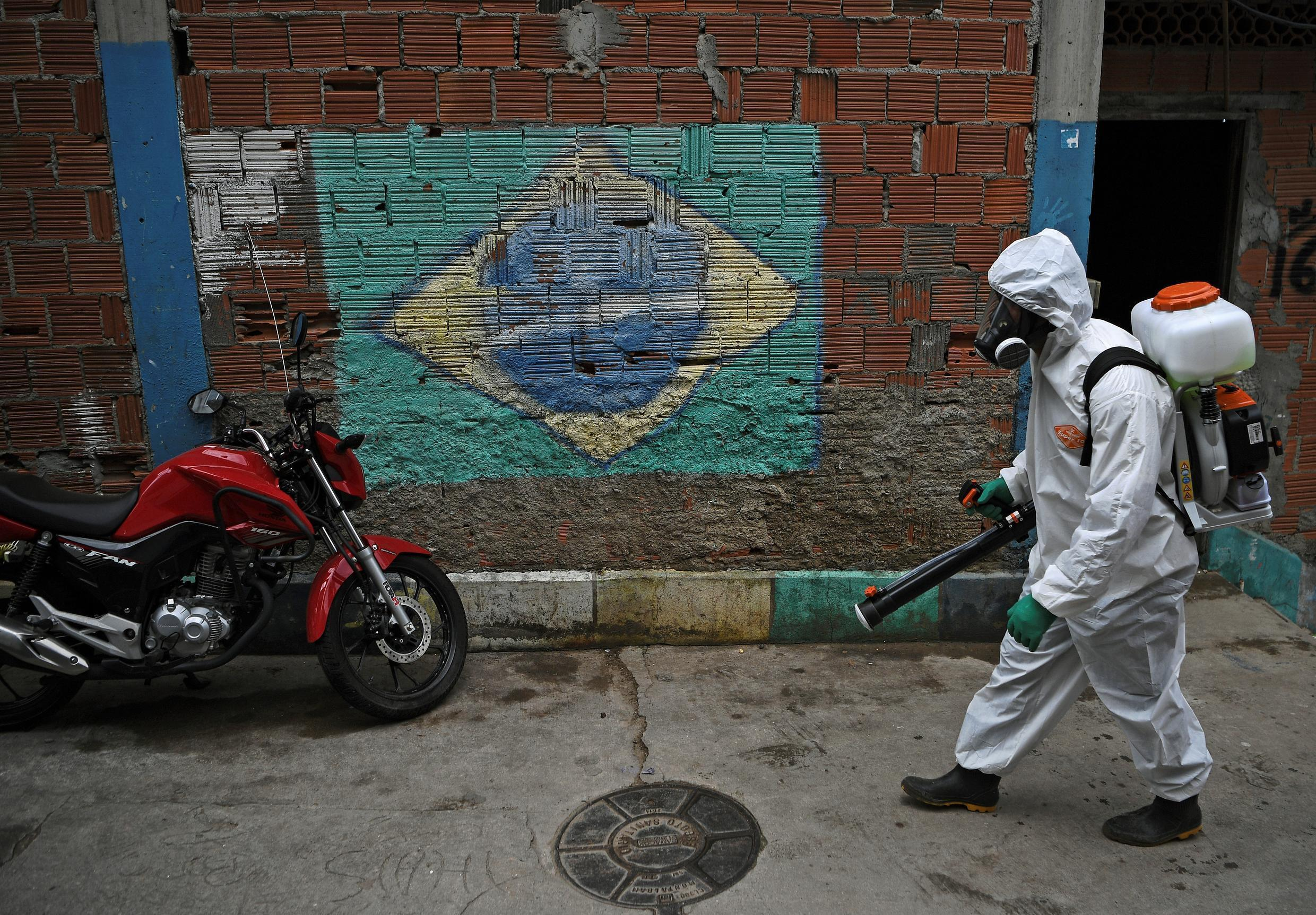 A volunteer walks past a mural of the Brazilian flag in April 2020 as he disinfects an area in Rio de Janeiro, Brazil.