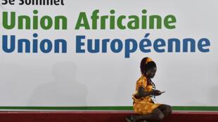 Une femme se tient devant la bannière du sommet Union africaine - Union européenne, à Abidjan, le 29 novembre 2017.
