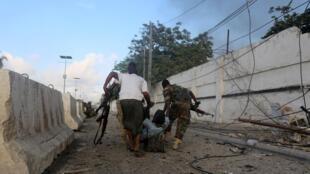 索馬里政府軍士兵從賓館中救出一名受傷的中學生 2015 11 1