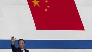Wen Jiabao waves in front of China's national flag, on the side of the aircraft that flew him to Pakistan, in Islamabad