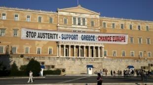 Parlamento grego em Atenas com cartaz durante manifestação pró-governo pedindo que os credores internacionais do país (FMI e UE) amenizem as cobranças.