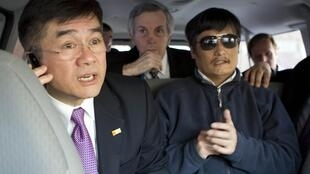 US Ambassador to China Gary Locke (L) talks on a mobile phone with blind activist Chen Guangcheng (R) in a car