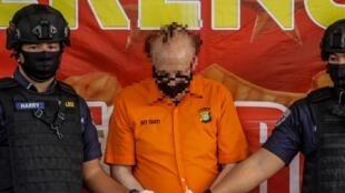 La police indonésienne avec le retraité français, après son arrestation, le 9 juillet 2020.
