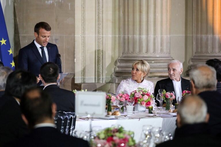 شارل آزناوور، ترانه سرا و خوانندۀ سرشناس فرانسوی در میهمانی شام رئیس جمهوری فرانسه و همسر او، بریژیت ماکرون، (که در کنار شارل آزناوور نشسته است) به افتخار ولیعهد ژاپن در کاخ ورسای - ١٢ سپتامبر ٢٠١٨