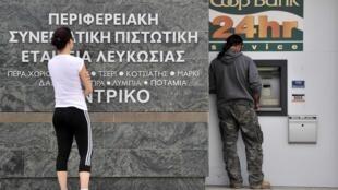 Pessoas diante de um banco 24 horas em Nicósia, neste sábado (16).