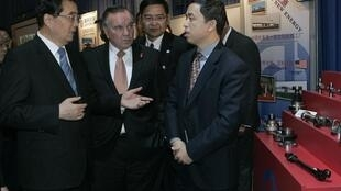 Le président chinois, Hu Jintao (G) parle au maire de Chicago (C) par l'intérmédiaire d'un interprète (D) lors d'une visite d'une société chinoise implantée au Etats-Unis, le 21 janvier 2011.