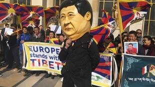 Tibetan activists and a likeness of Chinese President Xi Jinping demonstrate against China's human rights record in Paris, 25 March 2019.