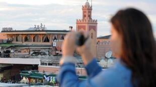 Une touriste prend en photo la place Djemaa el-Fna à Marrakech (Maroc). (Photo d'illustration)