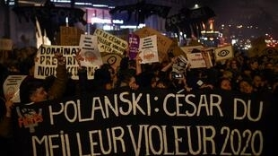 """Feminist activists hold a banner reading """"Polanski: Best rapist 2020 award"""" during a demonstration outside the Salle Pleyel in Paris as guests arrive for the 45th edition of the Cesar Film Awards ceremony on February 28, 2020."""