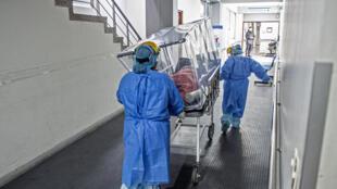 Personal sanitario trasladan a un paciente con coronavirus a la unidad de cuidados intensivos del hospital peruano Alberto Sabogal Sologuren, el 2 de julio de 2020 en Lima