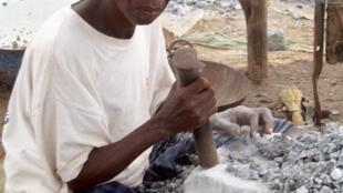Sur le site de Pissy, au cœur de la capitale burkinabé, une femme brise du granit pour le transformer en gravier qui sera ensuite revendu par petites quantités aux intermédiaires.