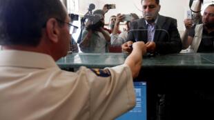 Un réfugié se fait tamponner son passeport pour traverser la frontière jordanienne vers la Syrie, le 15 octobre 2018 près de Mafraq.