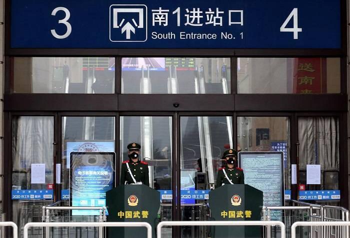 """مأموران چینی که ماسک پوشیدهاند، جلو ورودی ایستگاه راهآهن در شهر """"ووهان"""" نگهبانی میدهند. این شهر به علت قرار گرفتن در مرکز شیوع ویروس کرونا، از طرف دولت چین به وضعیت قرنطینه درآمده و از مردم خواسته شده شهر را ترک نکنند."""