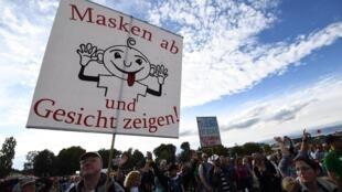 Manifestation à Berlin le 4 octobre 2020 de personnes contre le port du masque. On peut lire sur la bannière «démasquez-vous et montrez votre visage».
