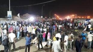 Les Soudanais observent un sit-in debout, de nuit à Khartoum.