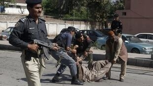 Security officials carry away an injured man from the site of a bomb blast in Peshawar, 29 March, 2013