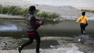 Una pareja de migrantes haitianos cruza el río Grande en un intento de llegar a Estados Unidos, cerca de El Paso, en Ciudad Juárez (México), el 15 de abril de 2021