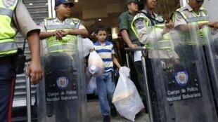 Au Vénézuéla, à Caracas, un enfant sort d'un magasin d'électroménager les bras remplis de sac, après le mesure du gouvernemnt de réduire les prix de 50%. Les policiers surveillent l'entrée.