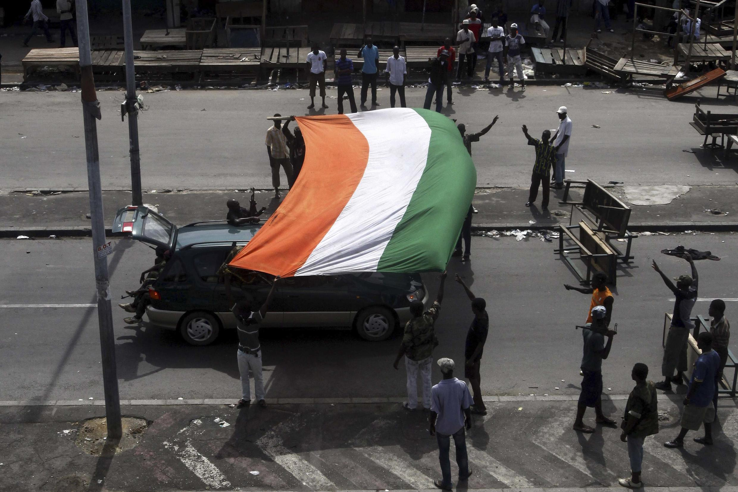Fighters loyal to Ivory Coast presidential claimant Alassane Ouattara celebrate with a national flag in the main city Abidjan.