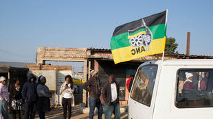 Un taxi arborant un drapeau de l'ANC passe devant un bureau de vote, le 3 août 2016, dans le township de Diepsloot à Johannesbourg.