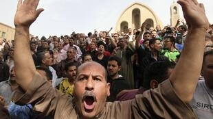 Coptic Orthodox Christians chant anti-Morsi and anti-government slogans as they attend the funeral of men who died during clashes between Muslims and Christians