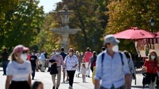 Ciudadanos con mascarilla pasean por el parque del Retiro, en Madrid, un soleado 10 de octubre de 2020