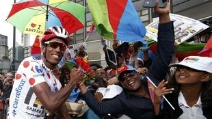 MTN-Qhubeka rider Daniel Teklehaimanot with Eritrean supporters before the start of the 8th stage.