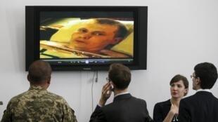 Украинские журналисты и военнослужащие просматривают видео со взятыми в плен россиянами, 18 мая 2015.