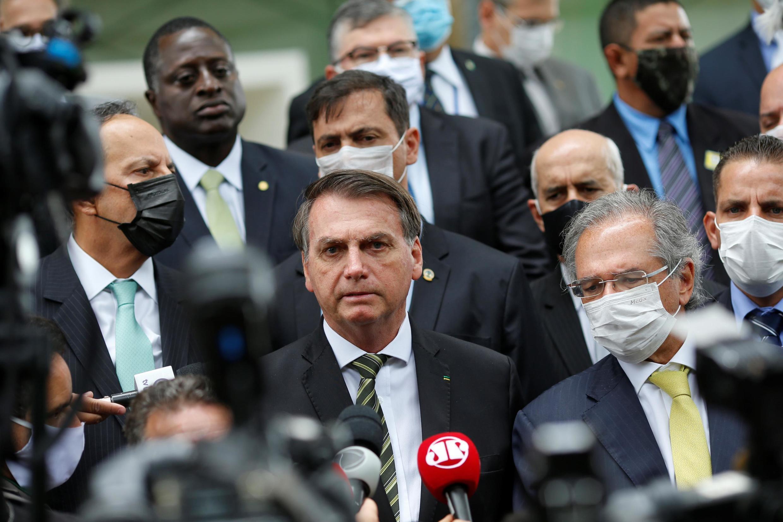 Le président brésilien Jair Bolsonaro aux côtés de son ministre de l'Économie masqué Paulo Guedes. Les deux hommes ont rendu visite au président de la Cour suprême le 7 mai à Brasilia, et alerté sur le risque d'effondrement économique du pays.