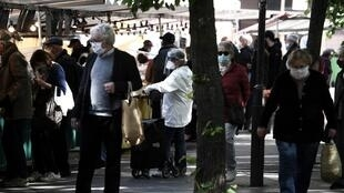 Customers shops at an outdoor market at the Place des Fetes in Paris on the second day of a lifting of confinement measures, 12 May 2020.