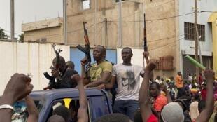 Des militaires maliens en civil applaudis lors de leur arrivée sur la place de l'Indépendance à Bamako, le 18 août 2020.