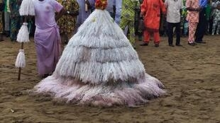 The masquerade-like Zangbetos are normally covered in synthetic palm tree fronds.
