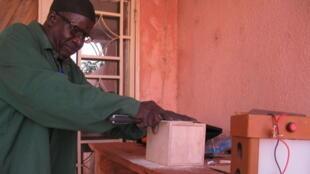 Ismaïla Diakité, menuisier d'Afrikasolar à Bamako, fabrique des lampes solaires avec du matériel de récupération.