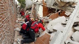 Bombeiros tentar encontrar sobreviventes entre os escombros
