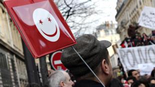 Manifestation Place de la République, à Paris. Un drapeau tunisien revisité et tout sourire...