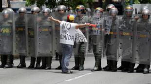 Manifestante de la oposición frente a miembros de la Guarndia Nacional en Caracas, el 18 de mayo de 2016.