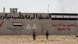 """Niños sirios ante un campo de refugiados llamado """"Container City"""", en la frontera turco-siria."""