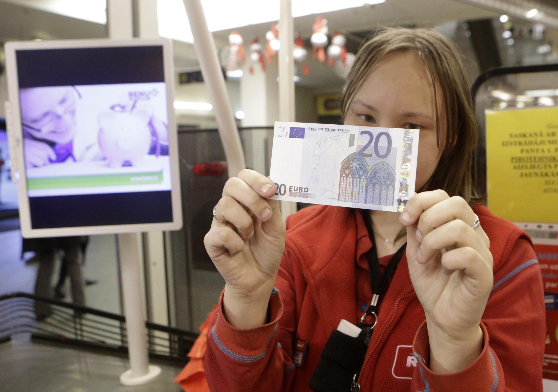 В супермаркете в Риге кассир рассматривает банкноту в 20 евро 01/01/2014