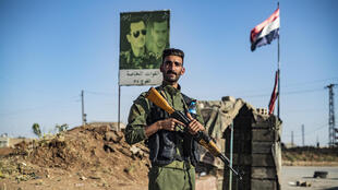 A member of the Syrian Kurdish internal security services known as Asayish stands at a joint checkpoint with Syrian government forces in the northeastern city of Qamishli