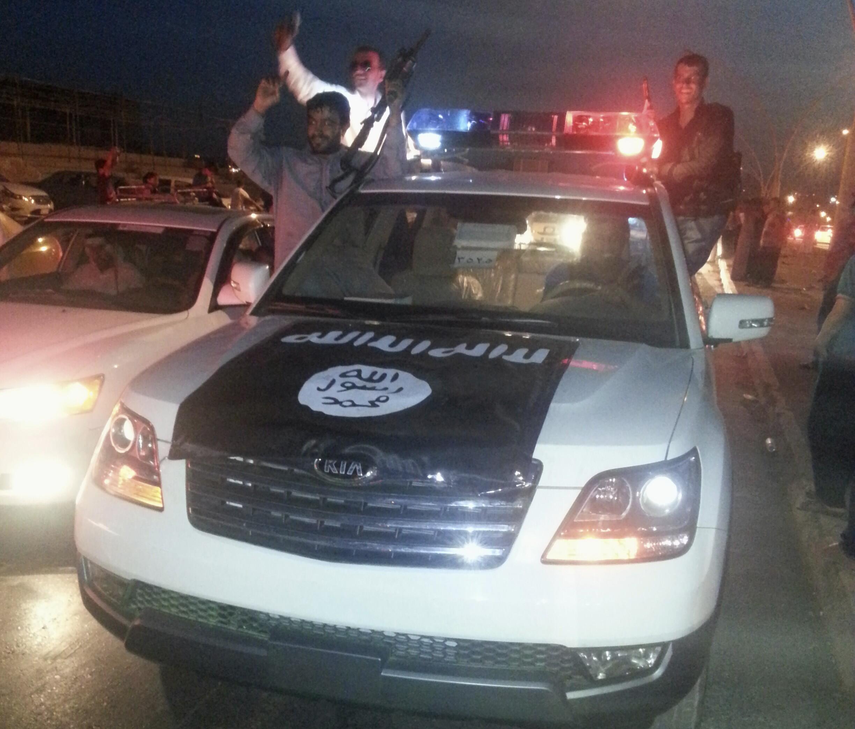 Des combattants de l'EIIL célèbrent leur victoire sur un véhicule pris à la police irakienne, ce 23 juin 2014.